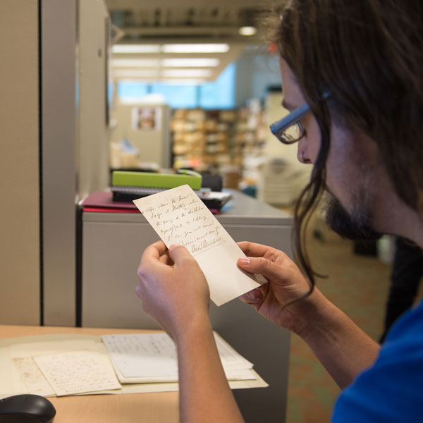 student working in the digitization centre at UBC examines archival material